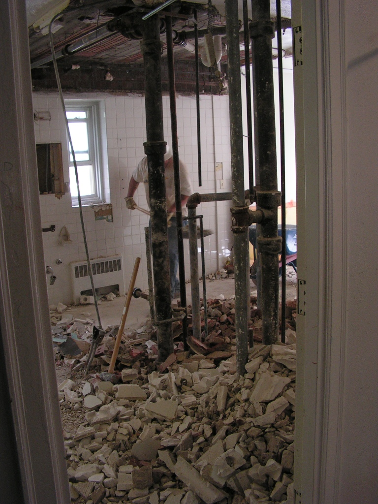 The bathroom separating the rooms is in the process of being demolished.